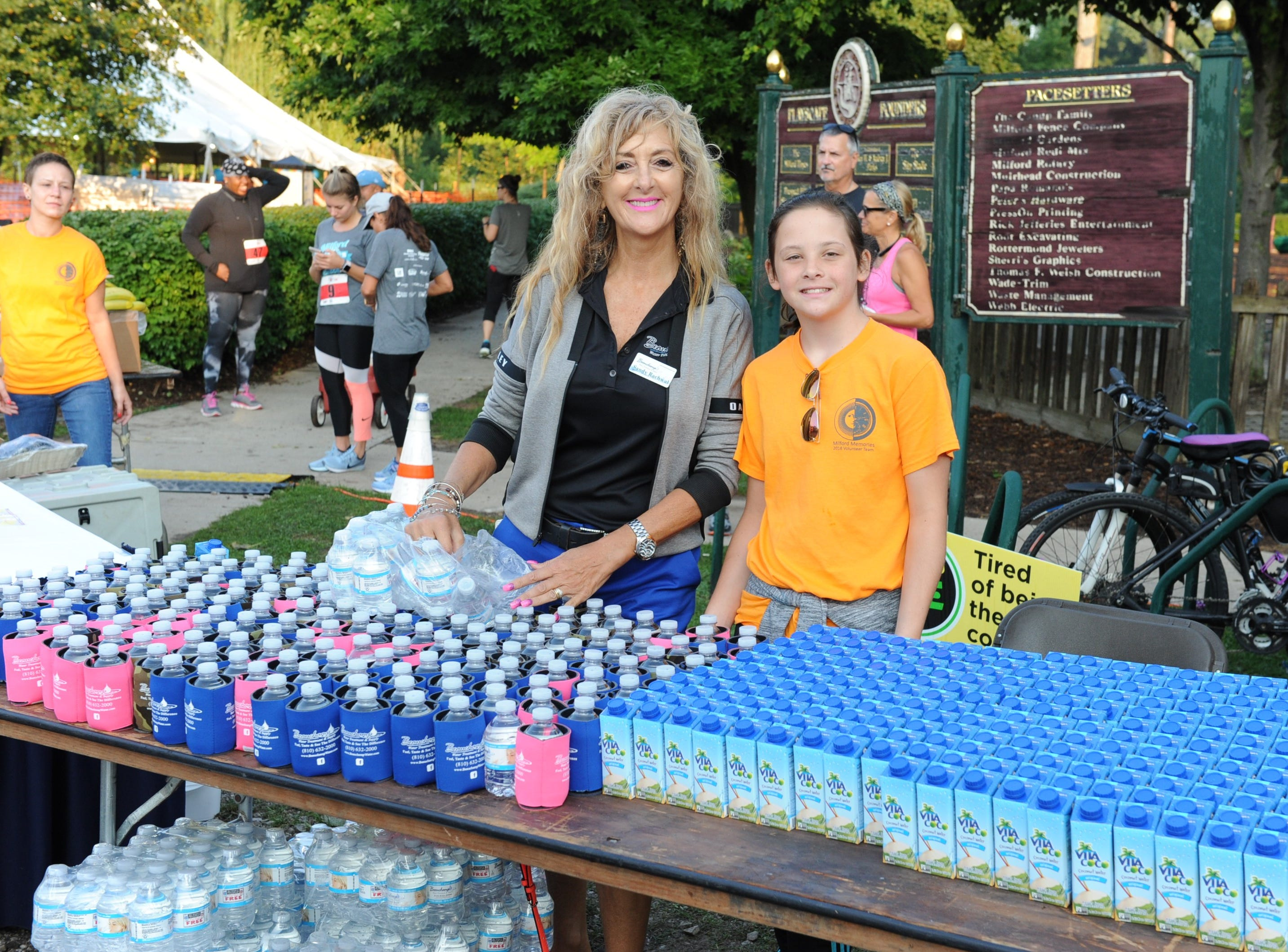 Sandy Rachwal and Emily Cryderman keep the runners hydrated Sunday morning in Milford.