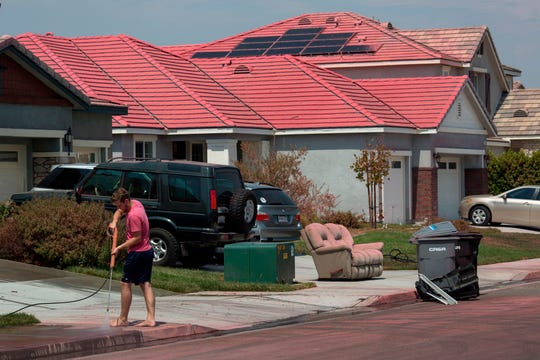 A man cleans up red fire retardant that was dropped on houses by a firefighting jet, as some residents who were forced to flee the Holy Fire return to their homes in Lake Elsinore, California on August 12, 2018. - The fire has burned 21,473 acres and was 29 percent contained as of 8:30 a.m. Saturday, according to the Cleveland National Forest.