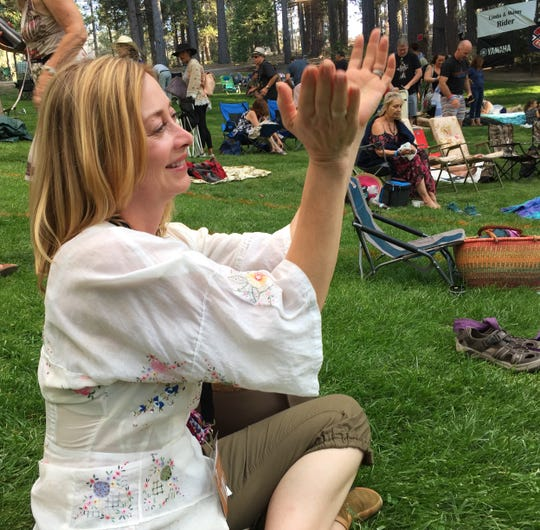 Actress Sharon Lawrence, who owns an Idyllwild home that was saved from the Cranston fire by Idyllwild firefighters, applauds a band Saturday in the Holmes Amphitheater at Jazz in the Pines