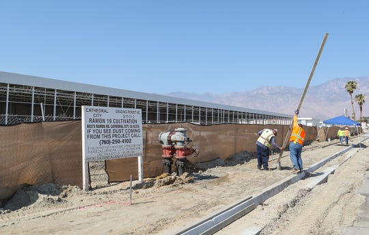 Workers work just outside a massive warehouse that's been constructed at 69375 Ramon Rd. in Cathedral City.  The project sign describes the property as Ramon 19 cultivation, August 13, 2018.