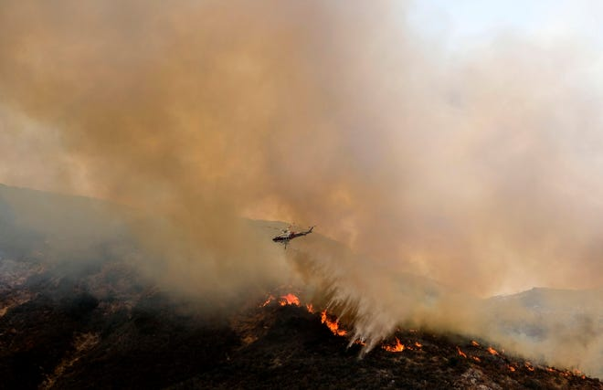 A helicopter drops water to a brush fire at the Holy Fire in Lake Elsinore, California, southeast of Los Angeles, on August 11, 2018. - The fire has burned 21,473 acres and was 29 percent contained as of 8:30 a.m. Saturday, according to the Cleveland National Forest.