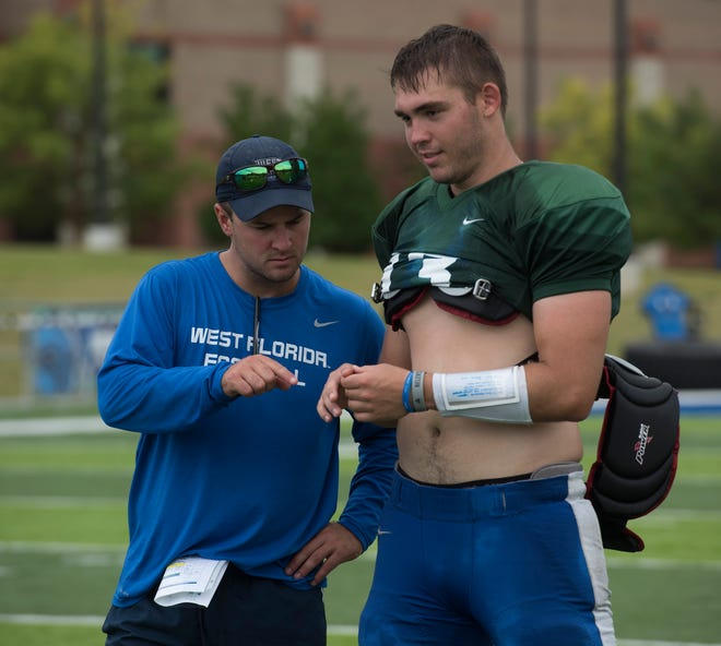 University of West Florida coach Kaleb Nobles checks on quarterback Mike Beaudry's hand at the close of practice on Friday, Aug. 10, 2018.