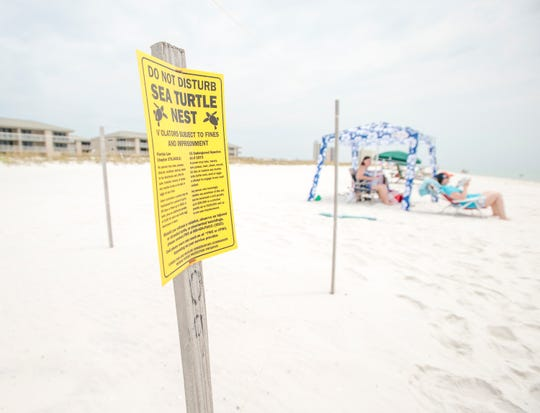 A sign warns about a sea turtle nest behind the Gulf Winds Condominiums in August 2018.