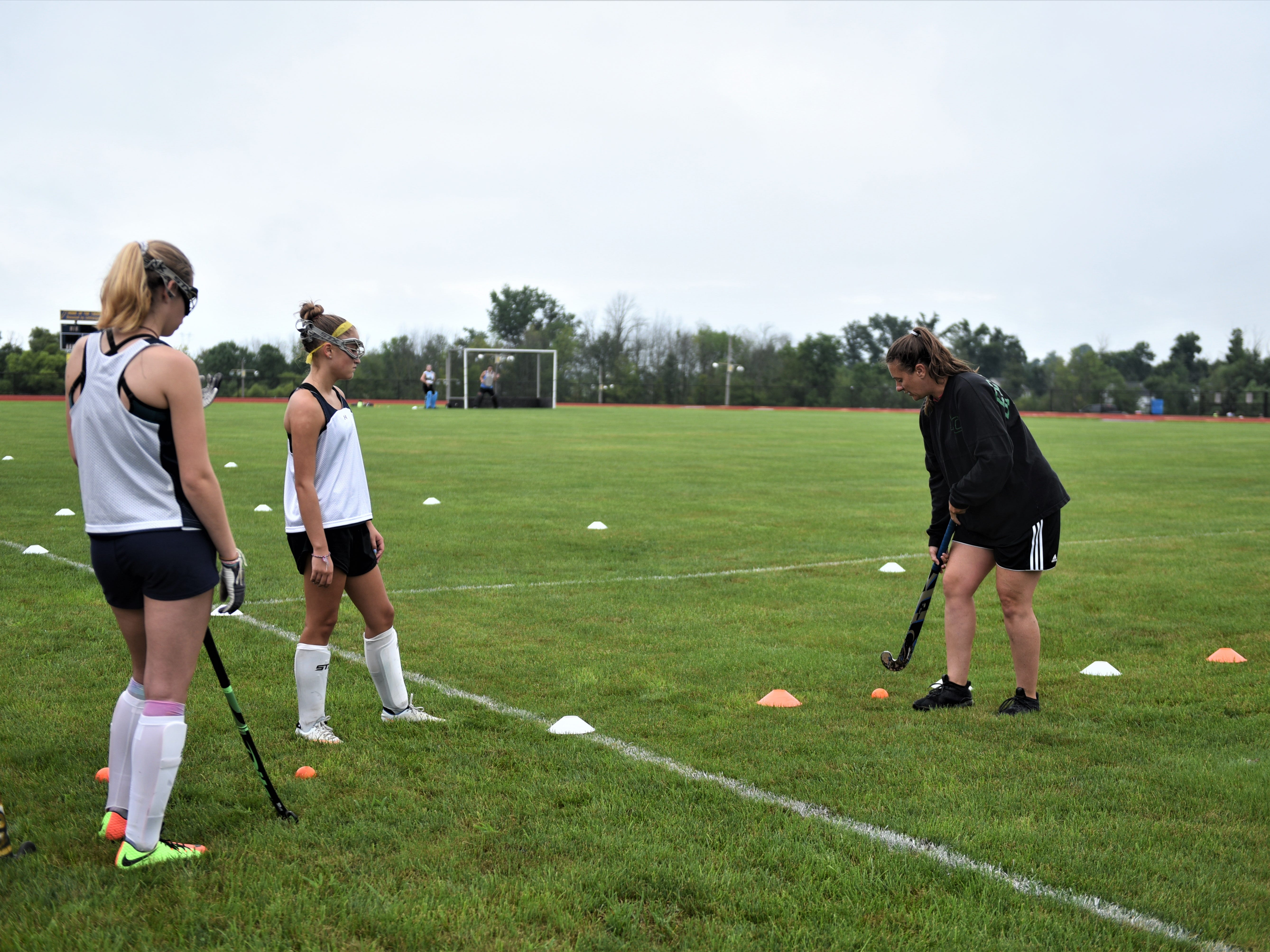 Littlestown field hockey coach Sara Lawyer demonstrates a drill to the team on the first day of fall sports on Monday, Aug. 13, 2018.