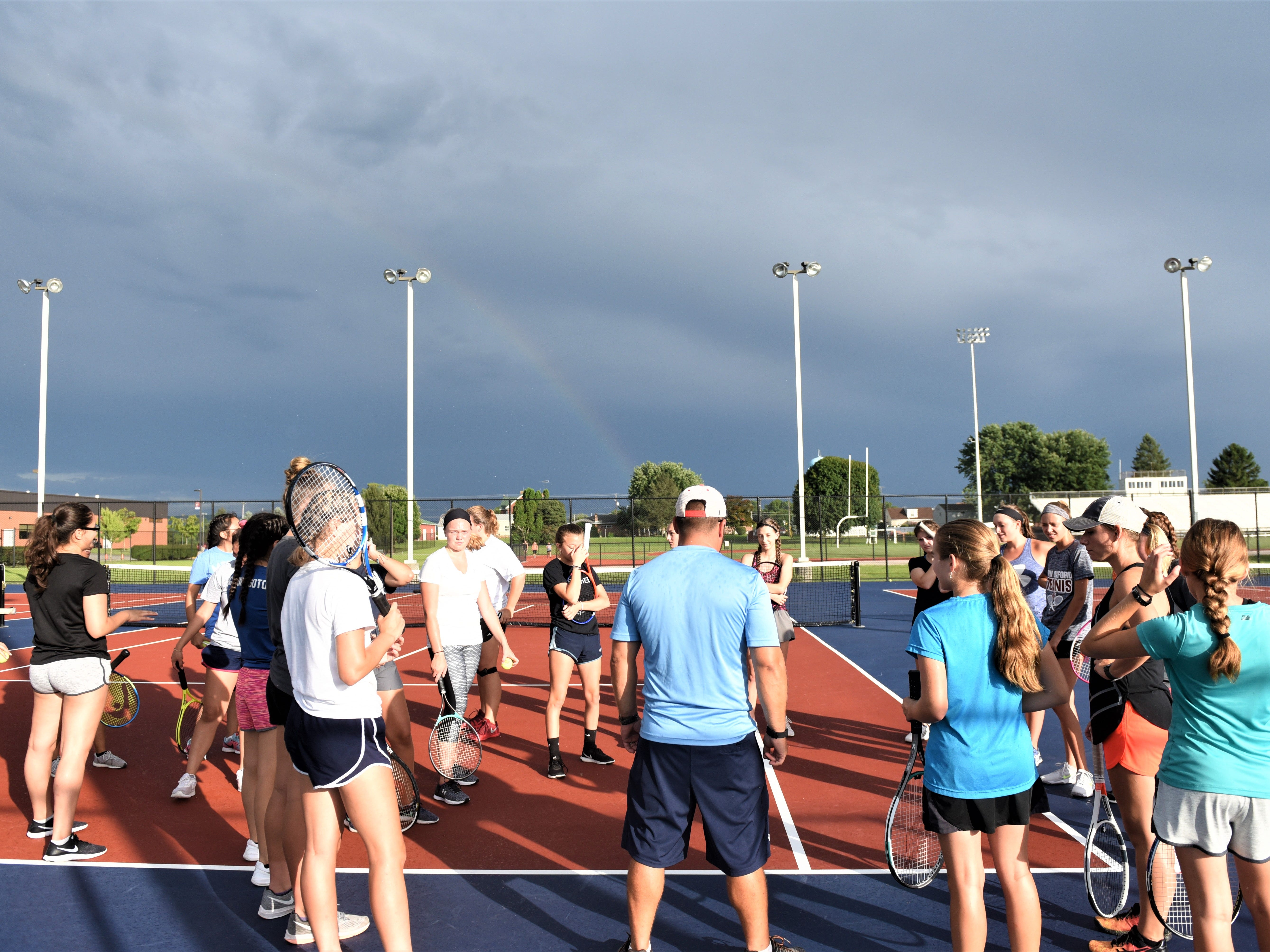 Coach Travis Martin and Assistant Coach Lauren Duffy start the New Oxford tennis season off under a rainbow on Aug. 13.