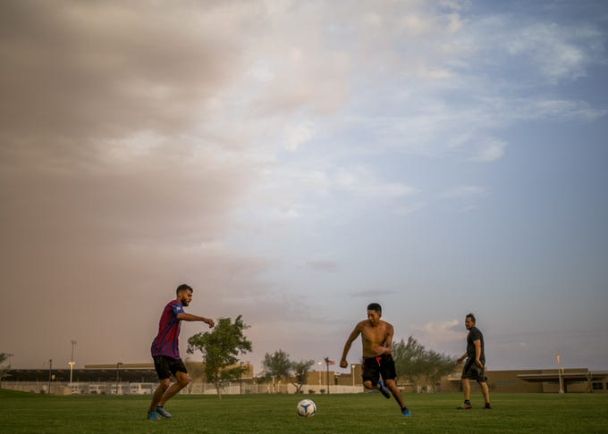 Rosendo Gonzalez (left), Emmanuel Jimenez (center) and Cristian Martinez (right) play soccer as a dust storm approaches near Estrella Foothills High School in Goodyear, Ariz. on Sun. Aug 12, 2018.
