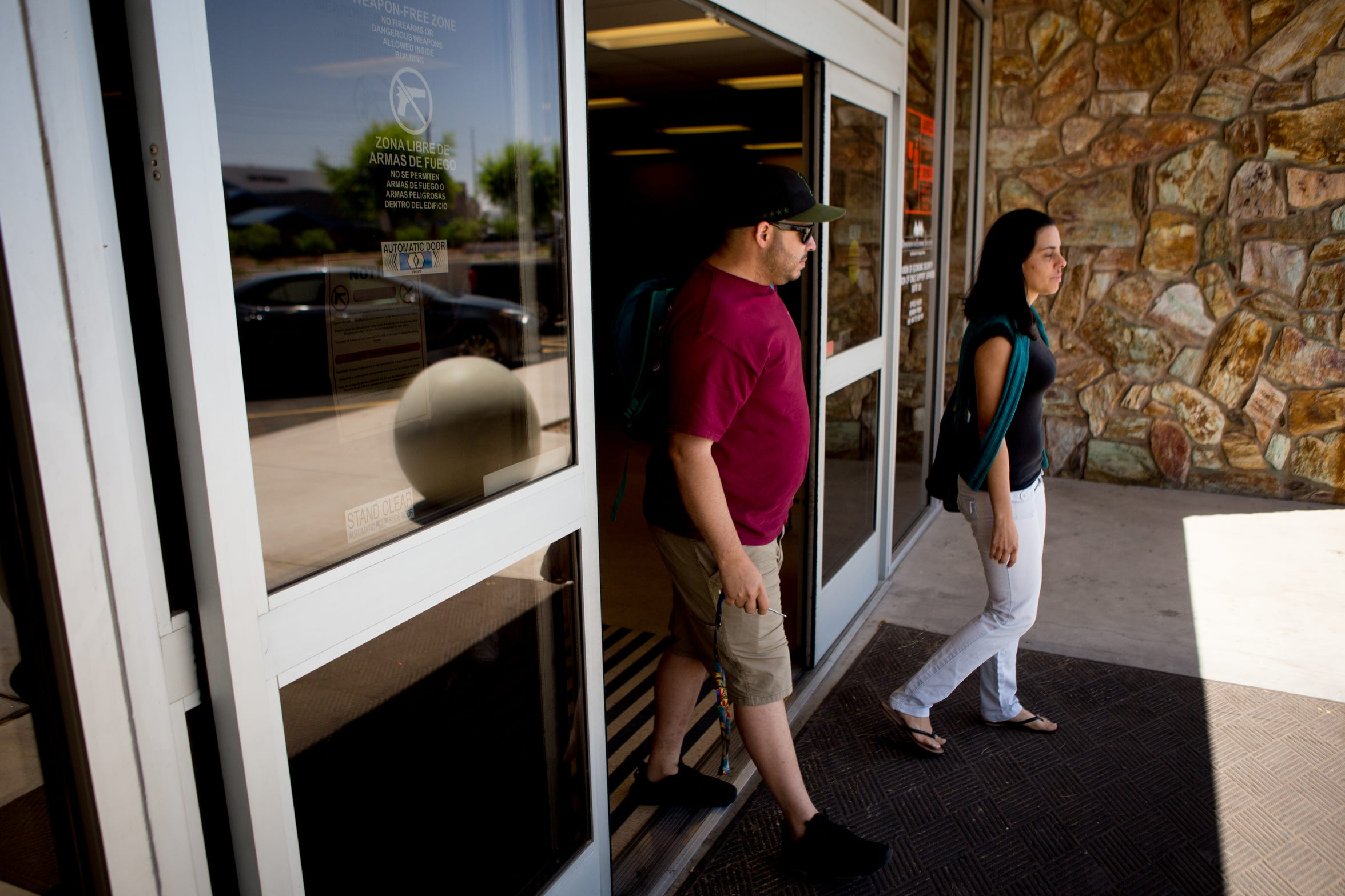 Aida Waleska Marquez and her childhood friend, Joel Sanchez, walk out of the Child Support Services office near their Phoenix apartment.