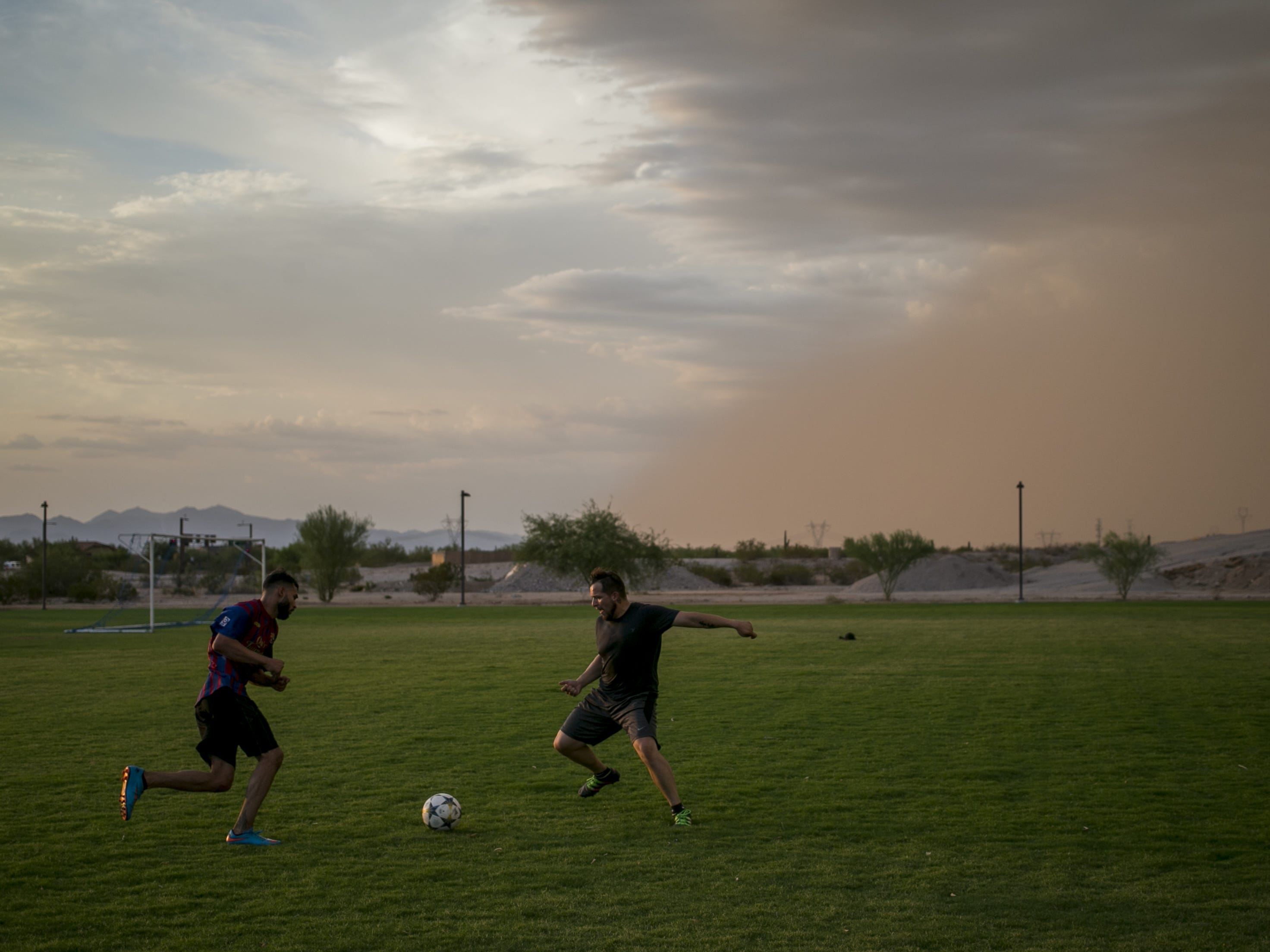 Cristian Martinez (right) and Rosendo Gonzalez (left) play soccer as a dust storm approaches near Estrella Foothills High School in Goodyear, Ariz. on Sun. Aug 12, 2018.