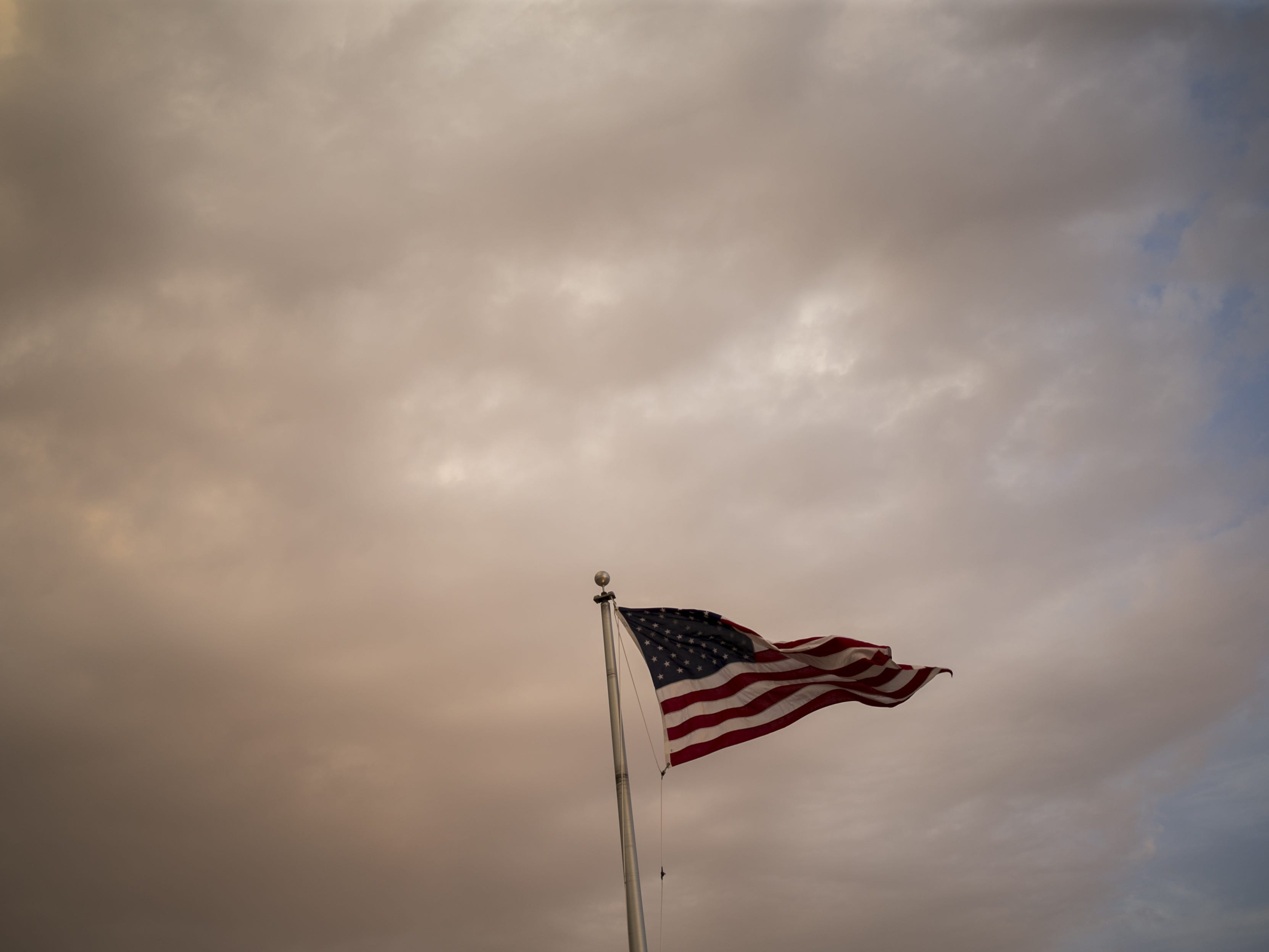 An American flag blows in the wind as a dust storm approaches Estrella Foothills High School in Goodyear, Ariz. on Sun. Aug 12, 2018.
