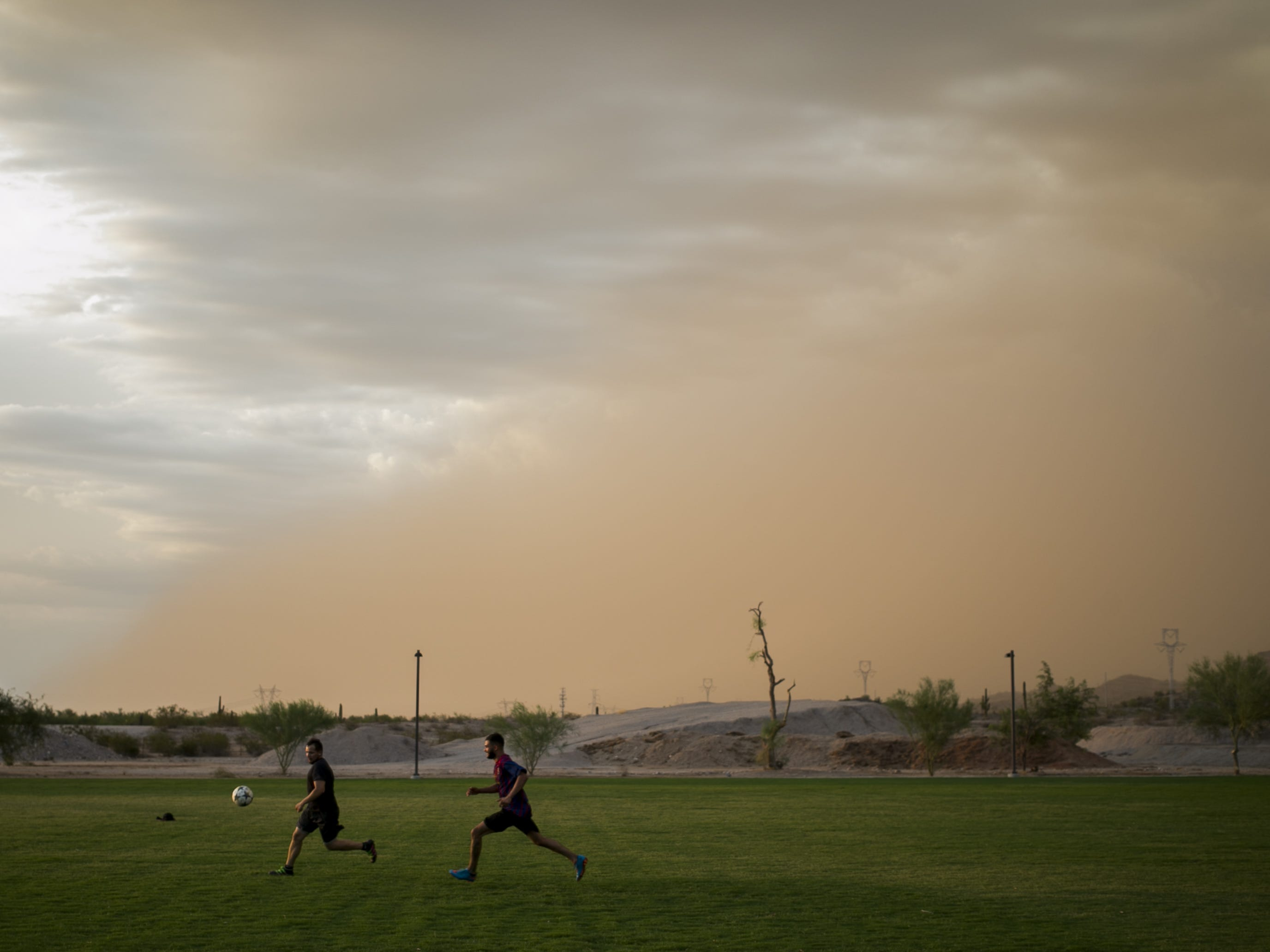 Cristian Martinez (left) and Rosendo Gonzalez (right) play soccer as a dust storm approaches near Estrella Foothills High School in Goodyear, Ariz. on Sun. Aug 12, 2018.