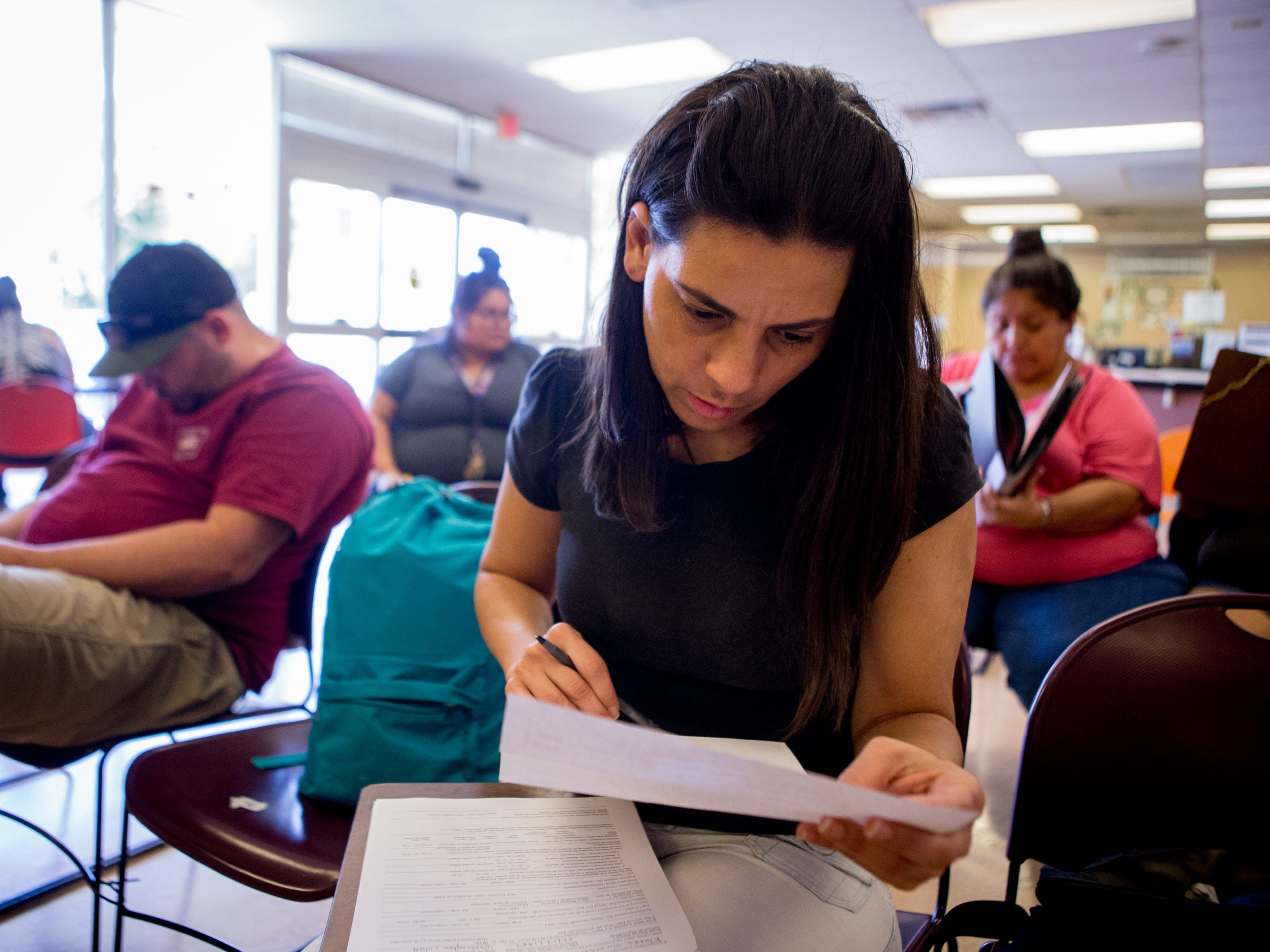 Aida Waleska Marquez fills out a 24-page packet at the Child Support Services office near her Phoenix apartment.