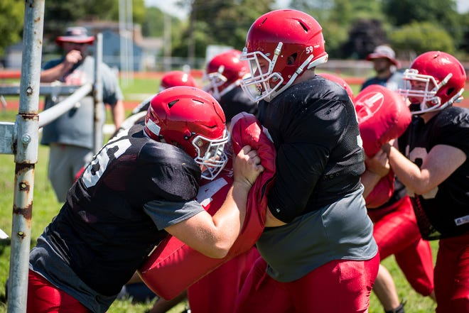 Port Huron defensive lineman Mathew Phillips, right, holds a pad while Austin Paehlig pushes against him during practice Friday, Aug. 10, 2018, at Port Huron High School.