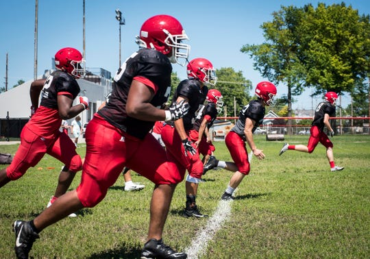 The Port Huron Big Reds football team start a practice by running across the field Friday, Aug. 10, 2018, at Port Huron High School.