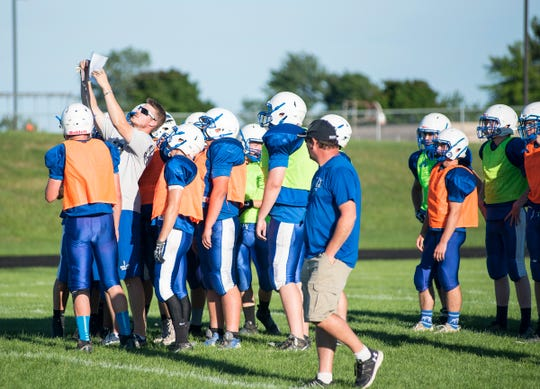 Croswell-Lexington football coach Garrett Grundman goes over plays with several members of the team during a scrimmage Friday, Aug. 10, 2018, at Cros-Lex High School.