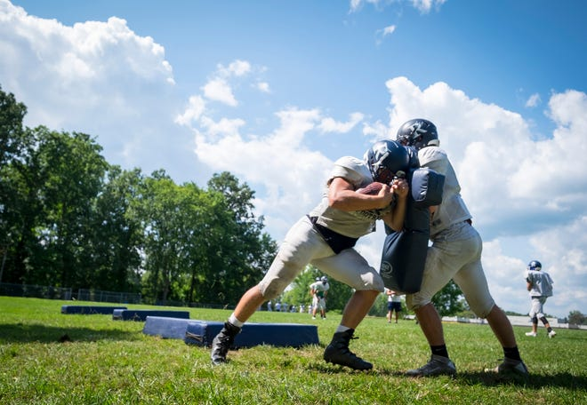 Richmond lineman Eric Barr, right, pushes against Andrew Ball with a pad during practice Monday, Aug. 13, 2018, at Richmond High School.