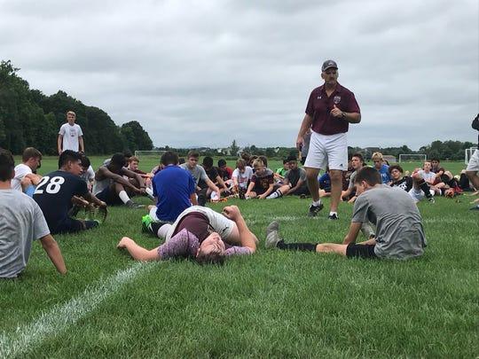 Arlington High School boys soccer coach Craig Sanborn addresses his team on the first day of practice Monday.