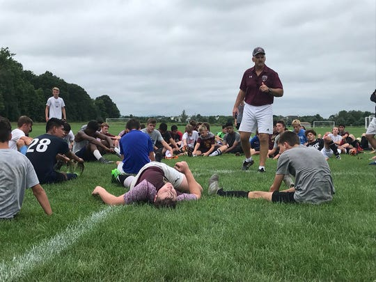 Arlington High School boys soccer coach Craig Sanborn addresses his team on the first day of practice Monday.