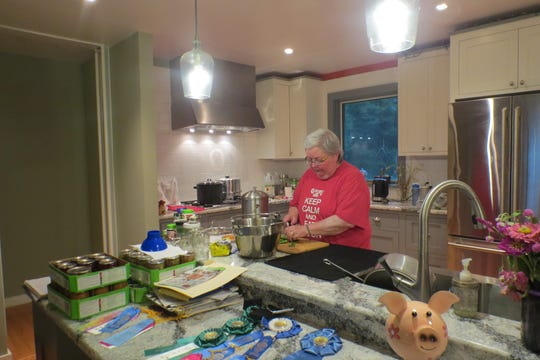 Terry Sennett works on a recipe in the kitchen of her Ghent home. Her winning fair ribbons can be seen in the foreground.