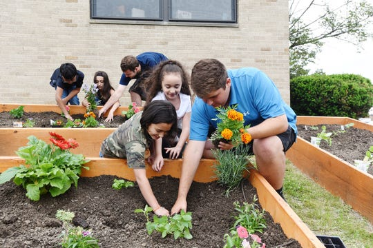 Mount Saint Mary College's students work on a sensory garden being created this summer at Bishop Dunn Memorial School.