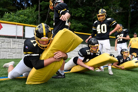 Elijah Workinger takes part in defensive drills during the first official day of fall practice in August. Workinger is the starting middle linebacker for the Lions this season.