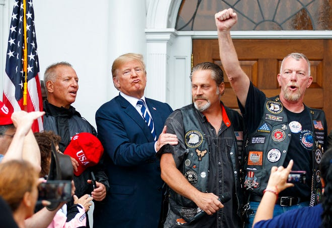 President Donald Trump stands in the rain with members of Bikers for Trump and supporters after saying the Pledge of Allegiance, Saturday, Aug. 11, 2018, at the clubhouse of Trump National Golf Club in Bedminster, N.J. Trump's hand is covering a Harley-Davidson racing patch on the man's shirt. (AP Photo/Carolyn Kaster)
