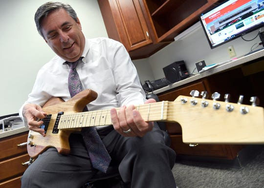 "Dr. Timothy Williams, York Suburban's new superintendent, keeps a hand made guitar, which he made at his last school, to practice his guitar lessons, strumming ""Smoke on the Water,"" Monday, August 13, 2018. John A. Pavoncello photo"