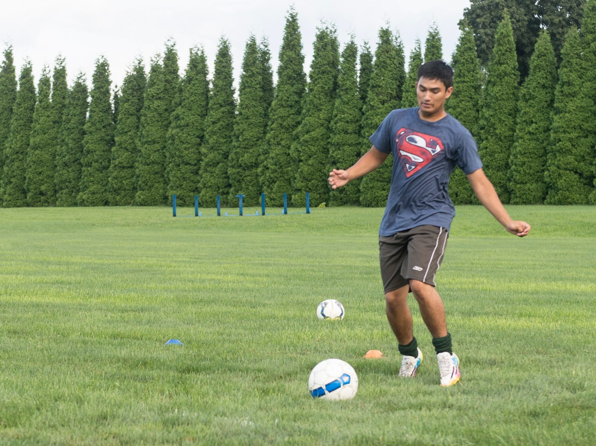 A York Catholic boys' soccer player runs through a passing and agility drill on August 13, 2018.
