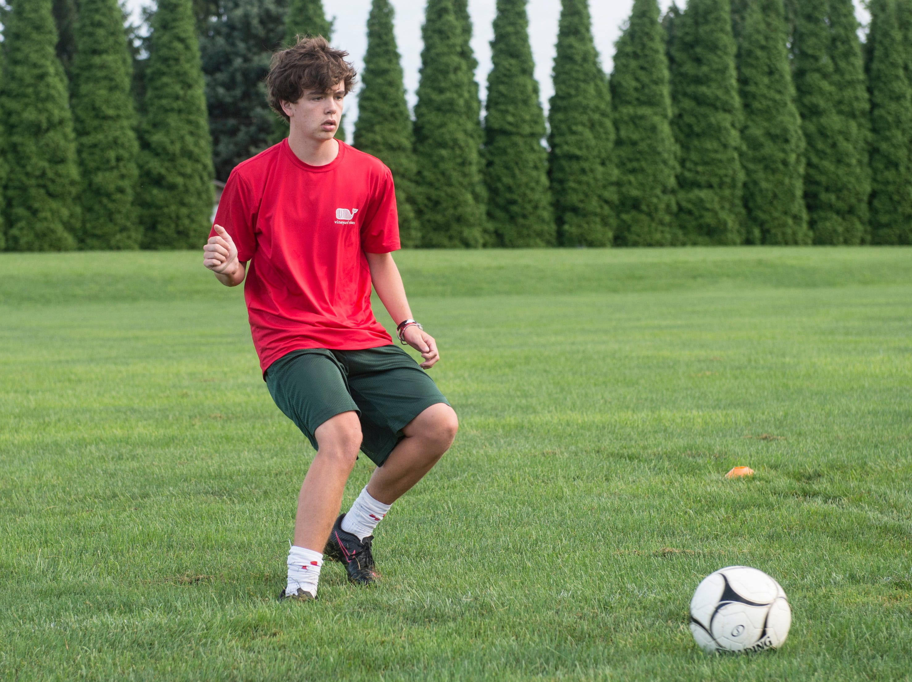 A York Catholic boys' soccer player works through a passing and agility drill on the first day of fall practice.