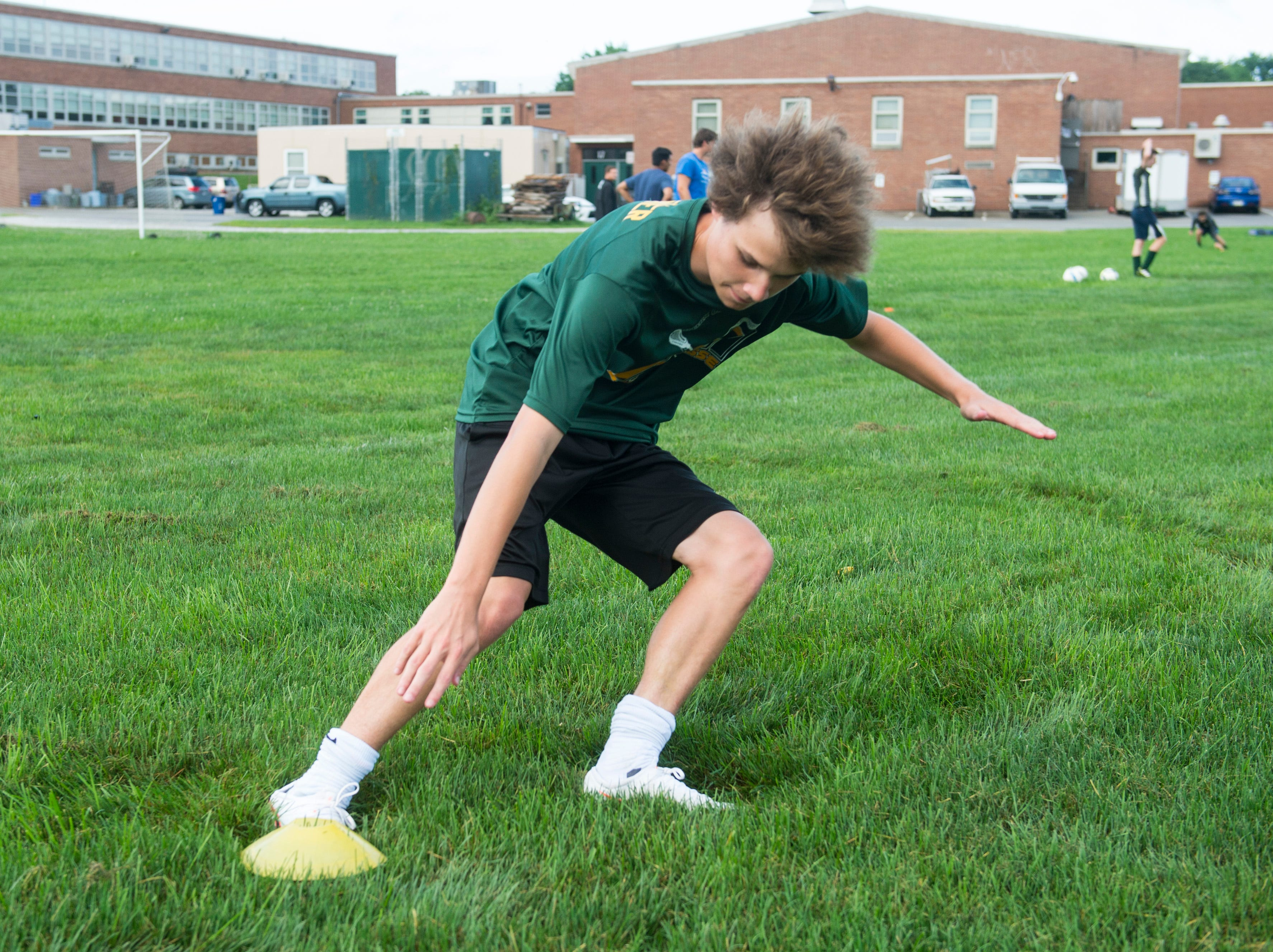 A York Catholic boys' soccer player runs through agility drills on the first day of fall practice.