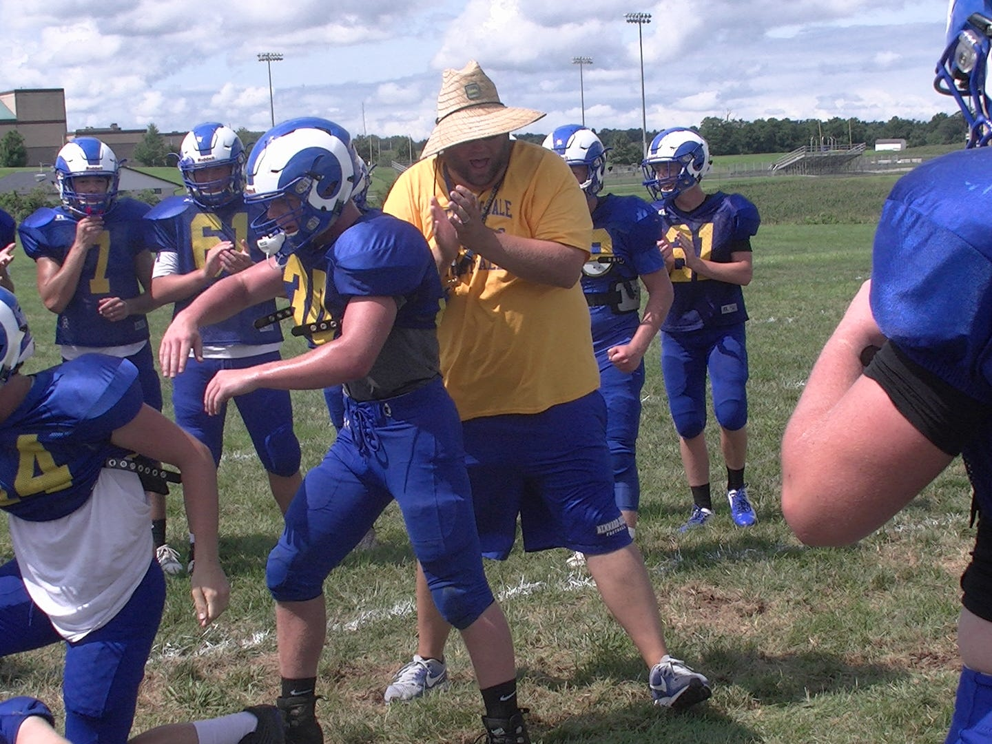 Kennard-Dale football coach Chris Grube applauds as Guy Shrewsbury and Ryan Gibney finish competing in a blocking drill at practice Monday.