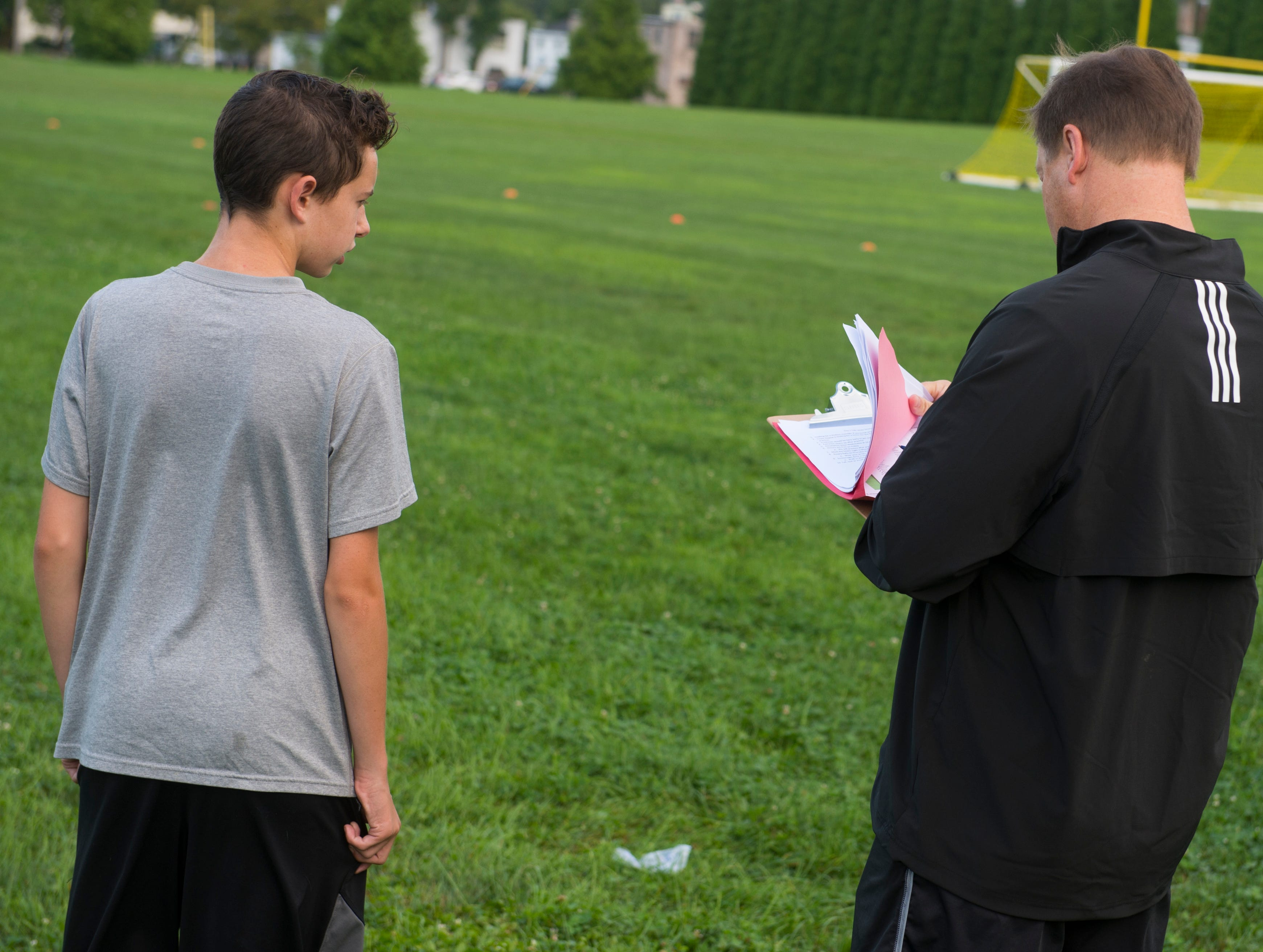 A young soccer player talks with York Catholic head coach joe Nattans.