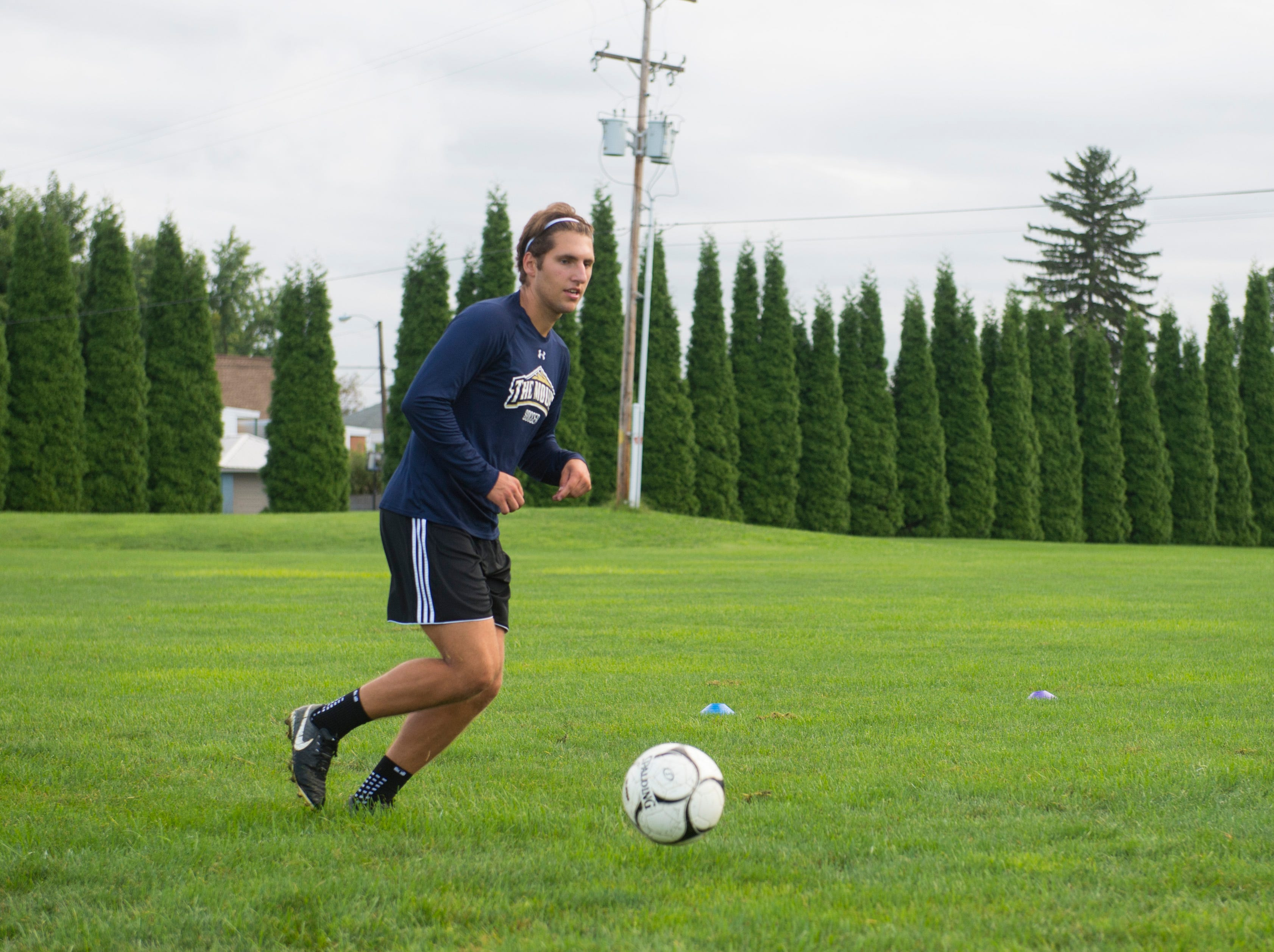 The York Catholic boys' soccer team runs through passing drills to start practice on August 13, 2018.