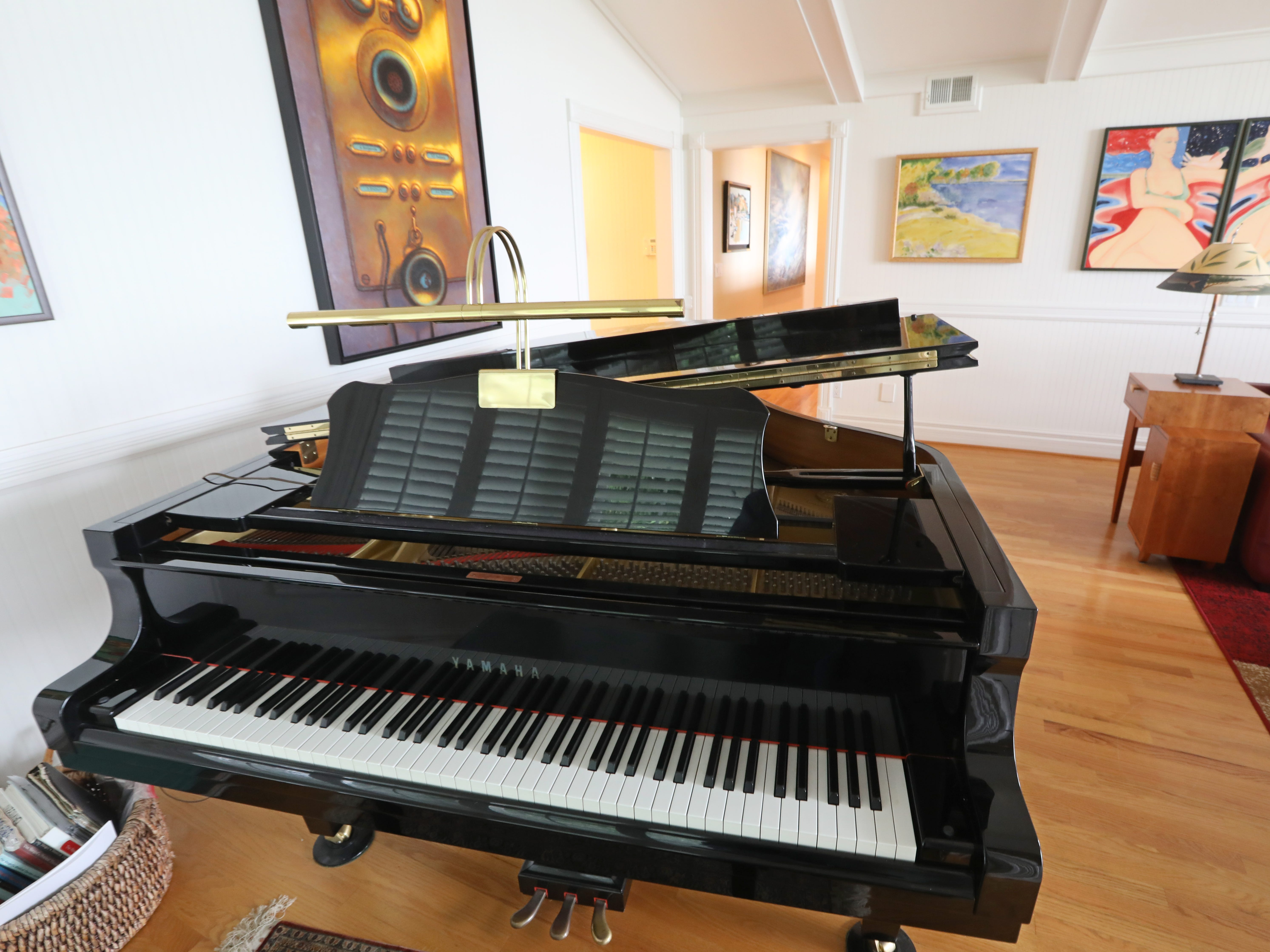 A grand piano is featured in the family room.