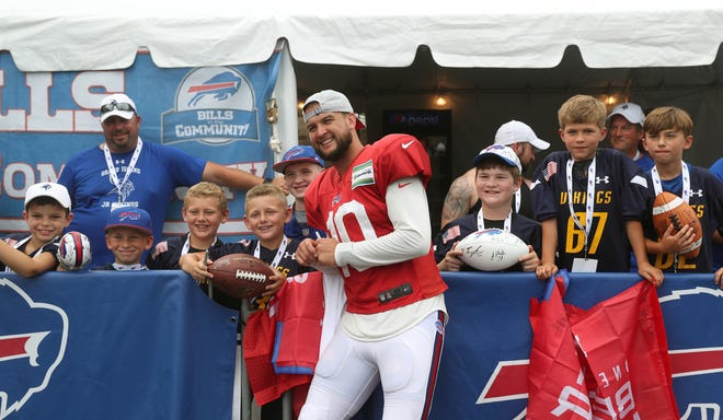 Bills quarterback AJ McCarron stops to pose for a photo with a group of children after practice.