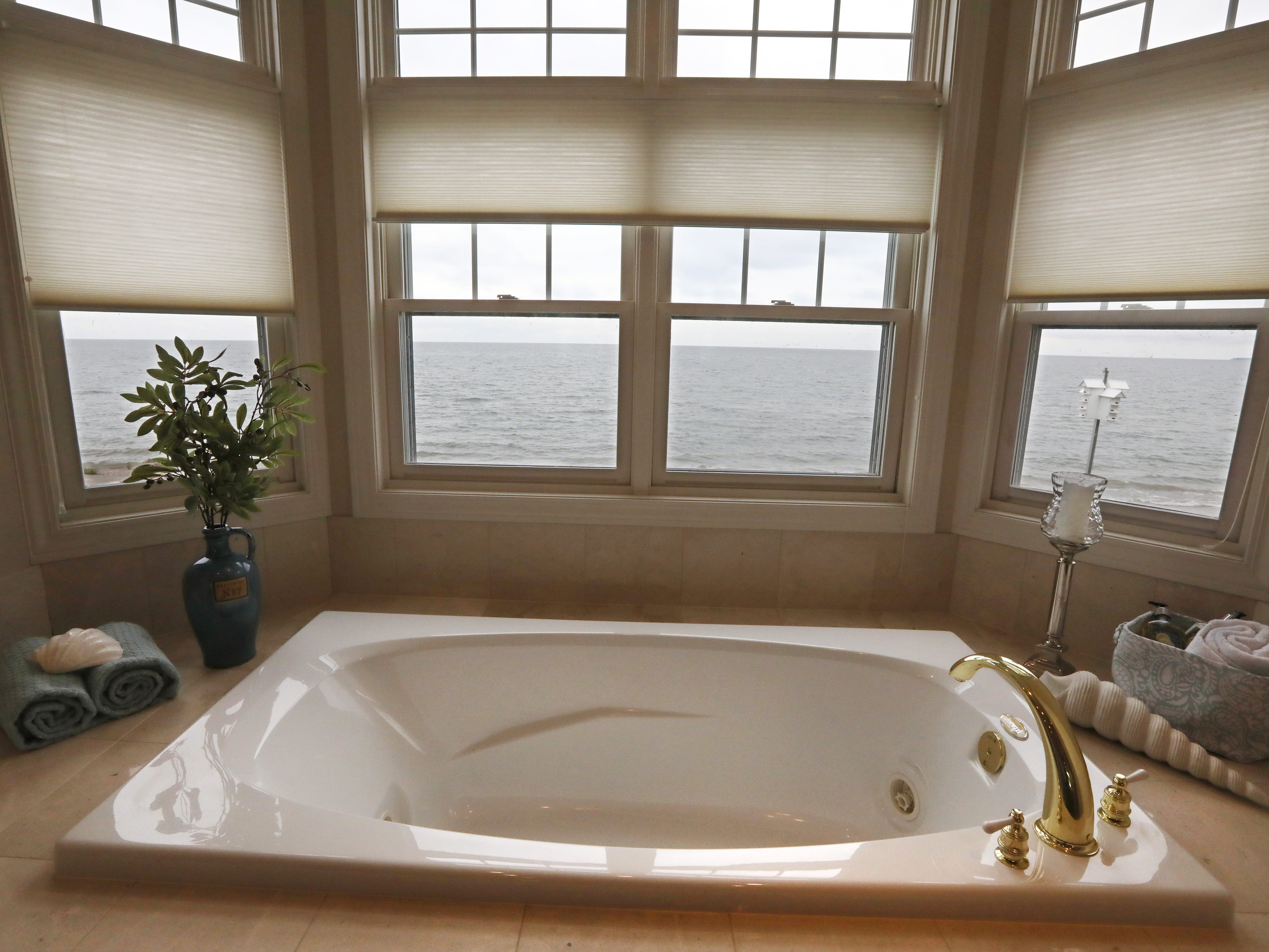 The master bathroom, featuring a large tub with a view of Lake Ontario, on the second floor.  The house features five full baths.
