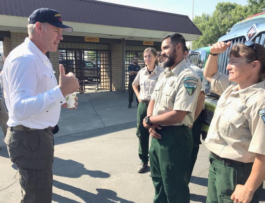 Interior Secretary Ryan Zinke, left, meets firefighters Monday at the Carr Fire incident command post at the Anderson fairgrounds.