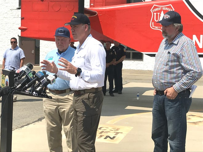 Agriculture Secretary Sonny Perdue, from left, Interior Secretary Ryan Zinke and Rep. Doug LaMalfa answer questions as a press conference Monday at the smokejumpers' base in Redding.