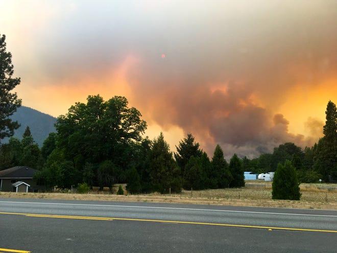 The Klondike Fire puts up smoke on Sunday night from U.S. Highway 199 in Selma, Oregon