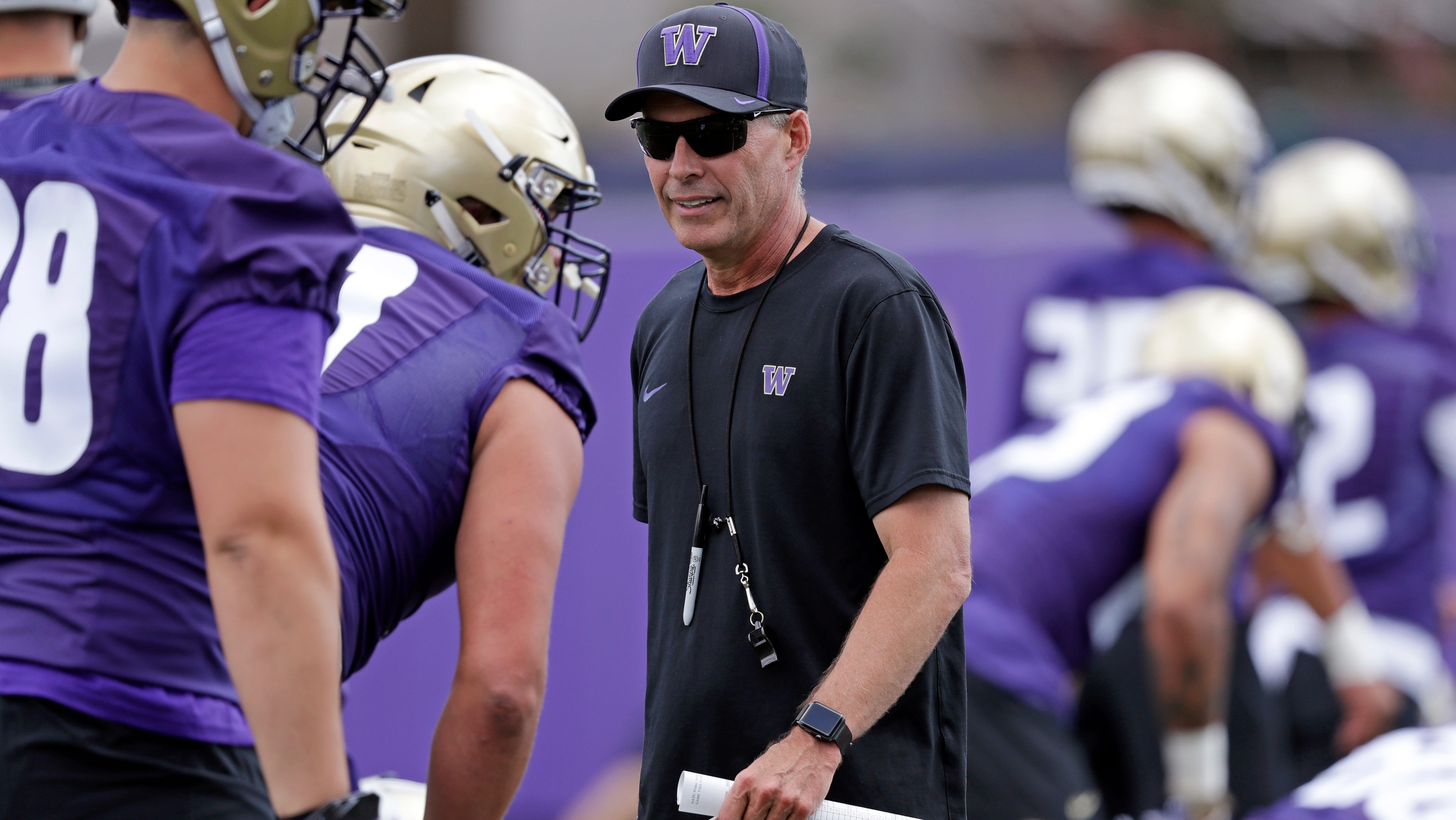 This Aug. 3, 2018, file photo shows Washington head coach Chris Petersen walking on the field during a team football practice in Seattle. Petersen's Huskies are the preseason favorites to win the Pac-12 with their roster full of NFL-caliber talent, but the entire league is looking for an improved season after going 1-8 in bowl games last winter.
