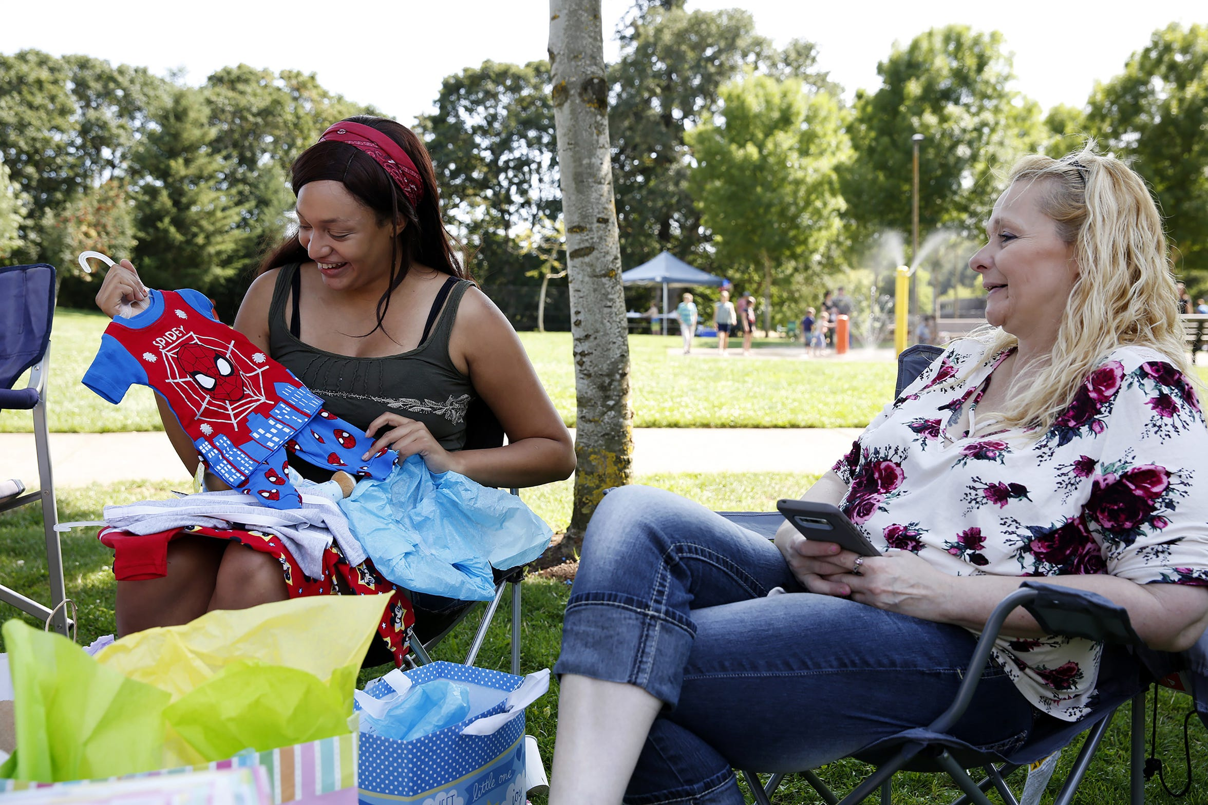 Marissa Brandt (left) opens a gift of Spider-Man pajamas as Lisa Ricks, the unborn baby's grandmother, looks on during Brandt's baby shower at Wes Bennett Park in Salem, Oregon, on Sunday, Aug. 12, 2018.