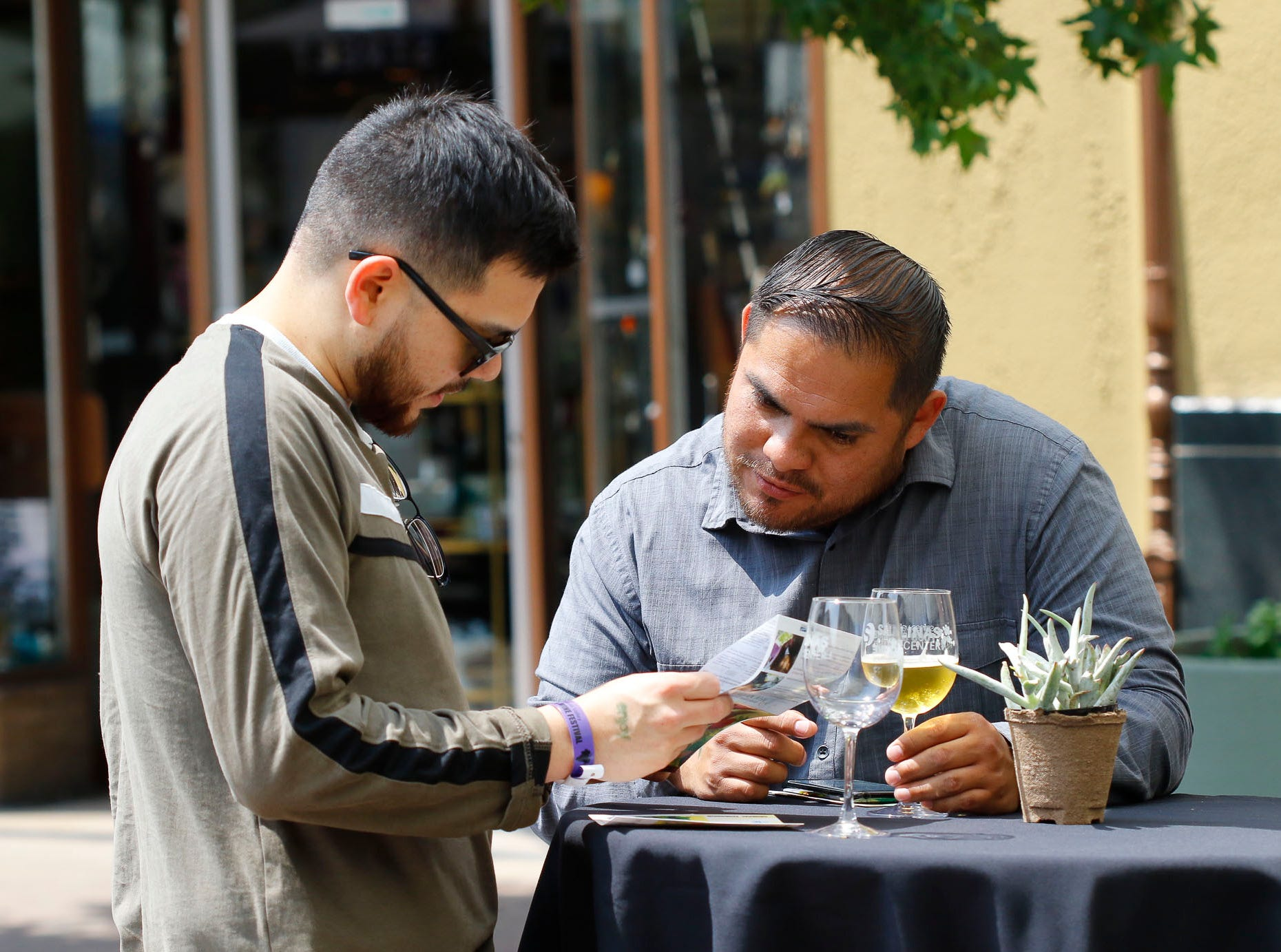 Attendees look over a brochure during the 2018 Salinas Valley Food and Wine Festival which takes place on Main Street in Old Town Salinas on Saturday, August 11, 2018.