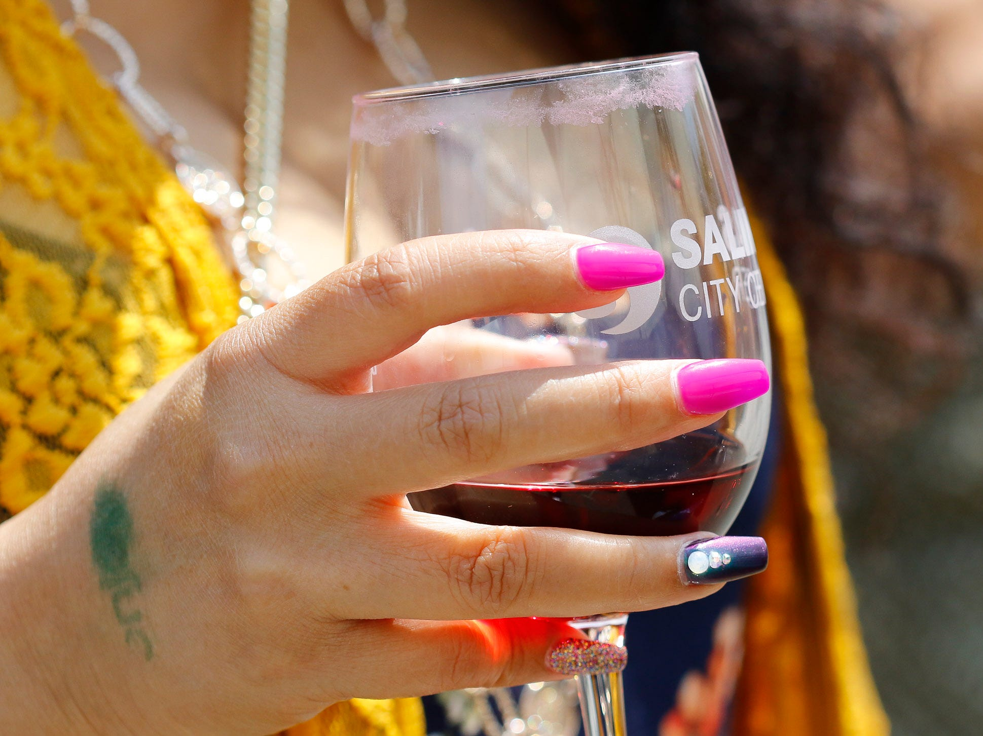 A woman walks while holding her wine sampling glass during the 2018 Salinas Valley Food and Wine Festival which takes place on Main Street in Old Town Salinas on Saturday, August 11, 2018.