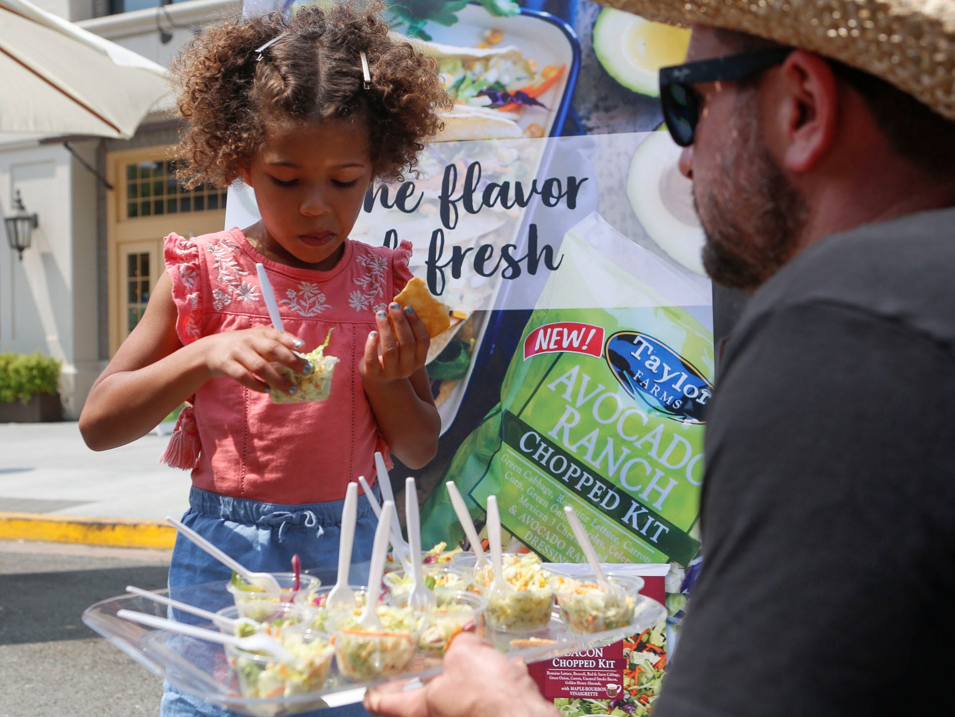 A young girl samples a Taylor Farms salad during the 2018 Salinas Valley Food and Wine Festival which takes place on Main Street in Old Town Salinas on Saturday, August 11, 2018.