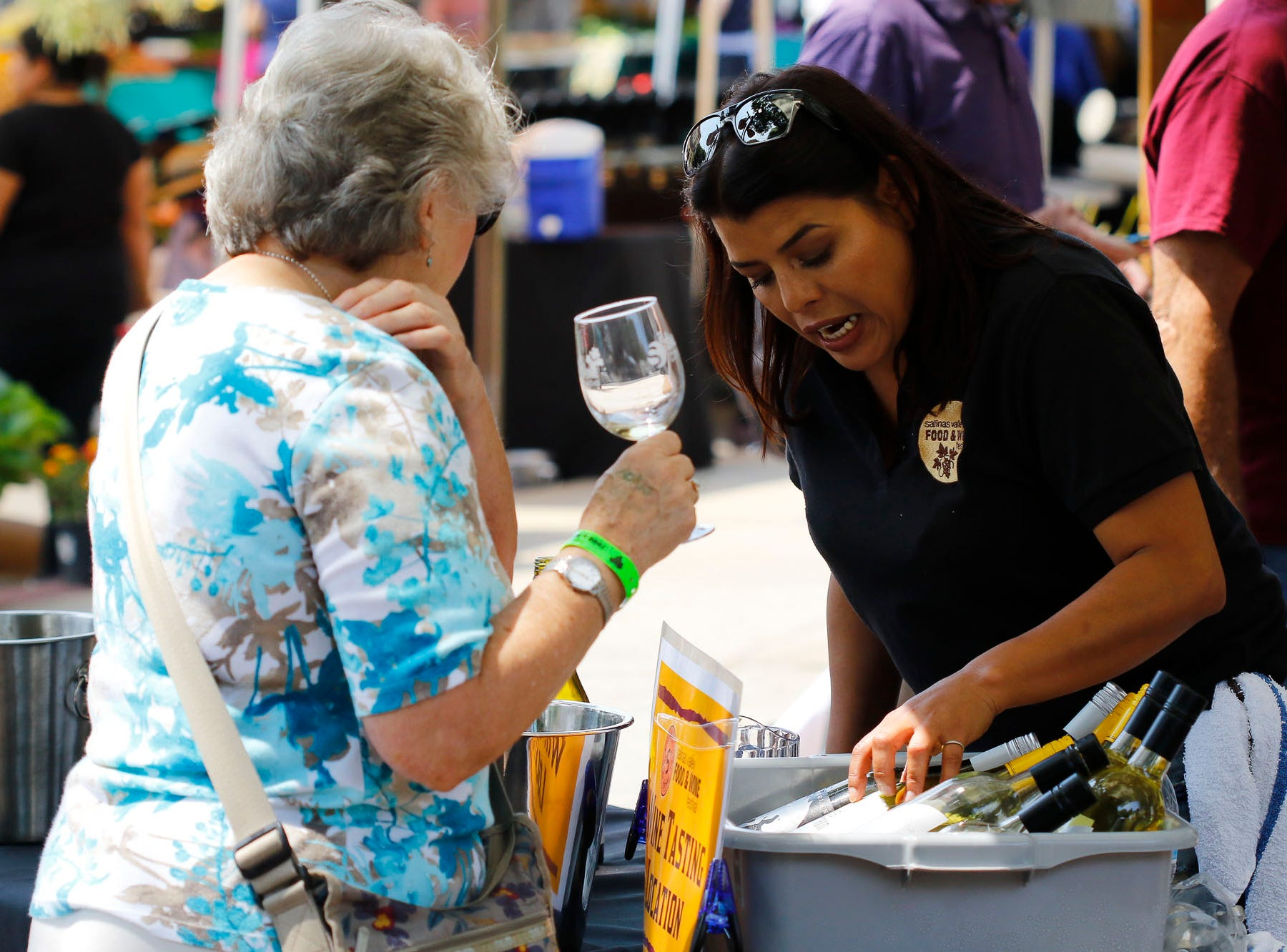 A woman working a sampling booth goes over bottles of wine with an attendee during the 2018 Salinas Valley Food and Wine Festival which takes place on Main Street in Old Town Salinas on Saturday, August 11, 2018.