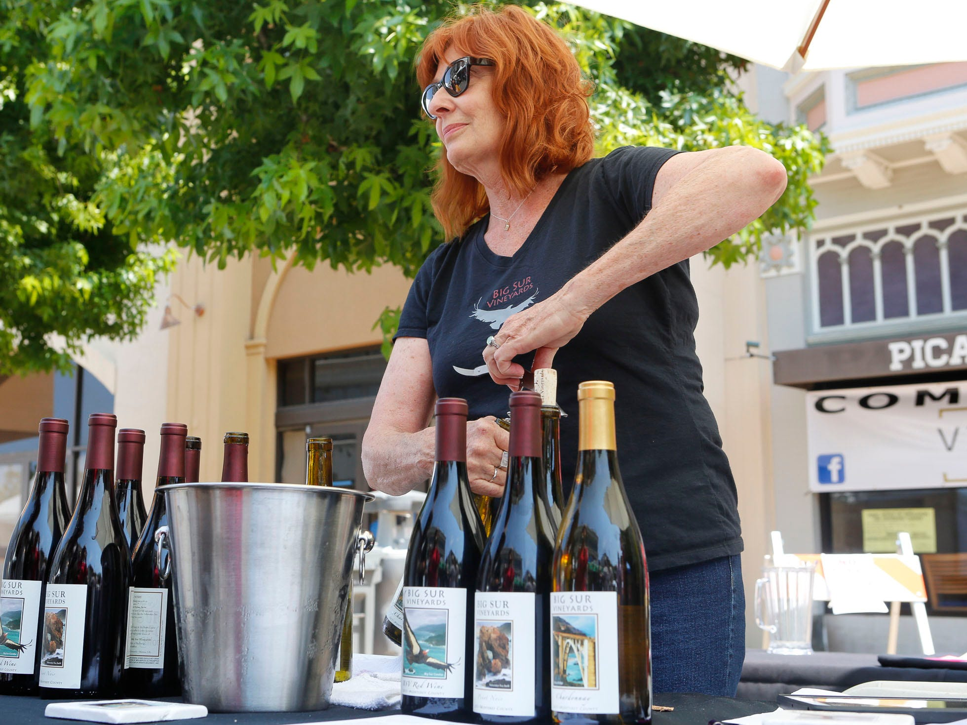 A vintner pulls a cork out of a bottle of wine during the 2018 Salinas Valley Food and Wine Festival which takes place on Main Street in Old Town Salinas on Saturday, August 11, 2018.