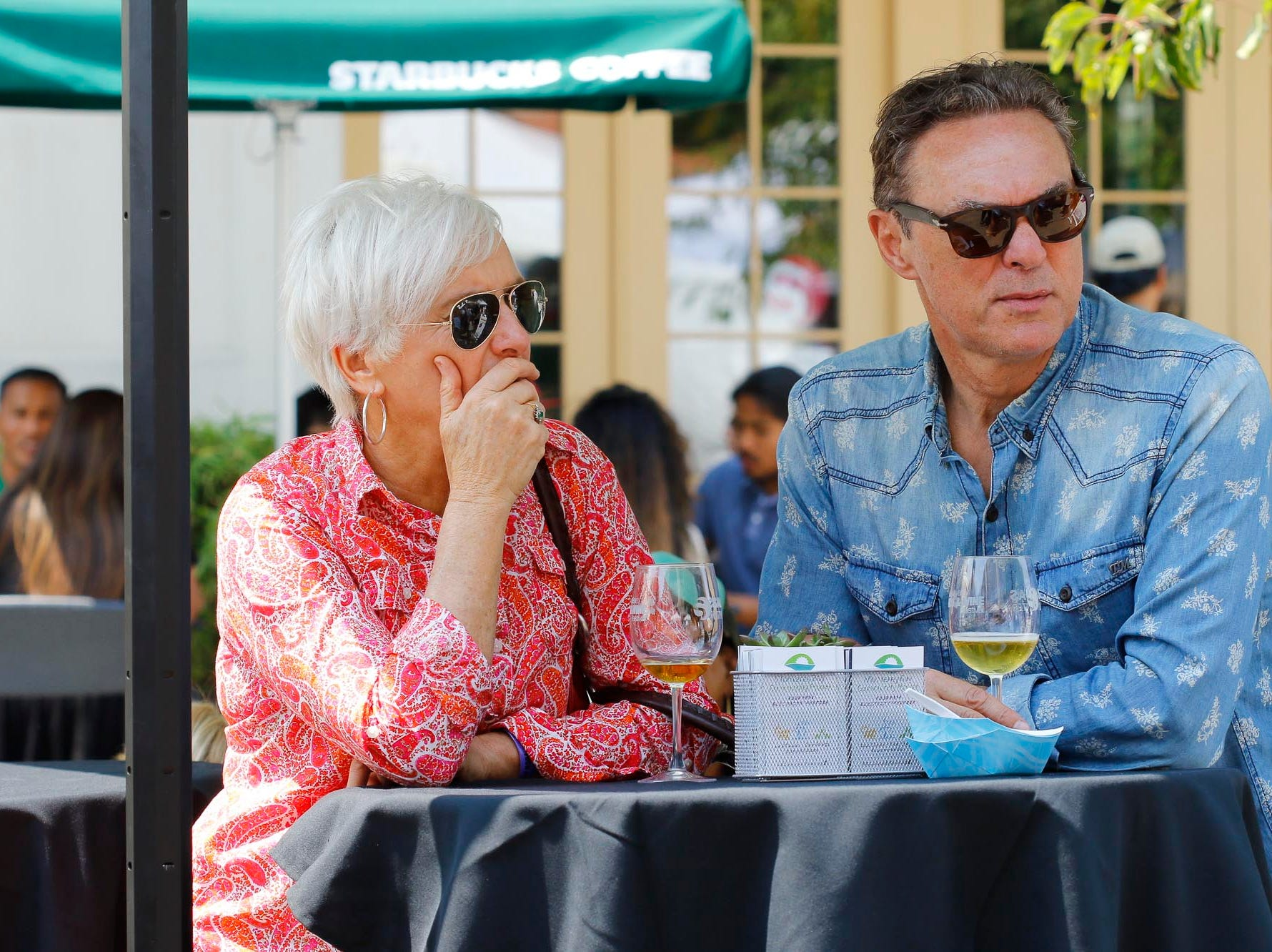 Two attendees look on as they pause from sampling during the 2018 Salinas Valley Food and Wine Festival which takes place on Main Street in Old Town Salinas on Saturday, August 11, 2018.