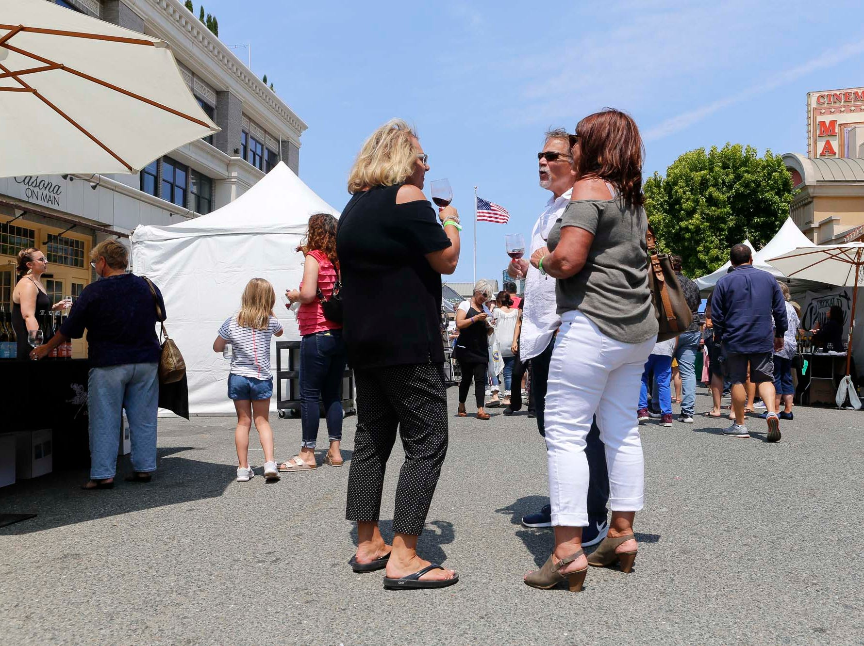 Attendees converse between sampling wines during the 2018 Salinas Valley Food and Wine Festival which takes place on Main Street in Old Town Salinas on Saturday, August 11, 2018.