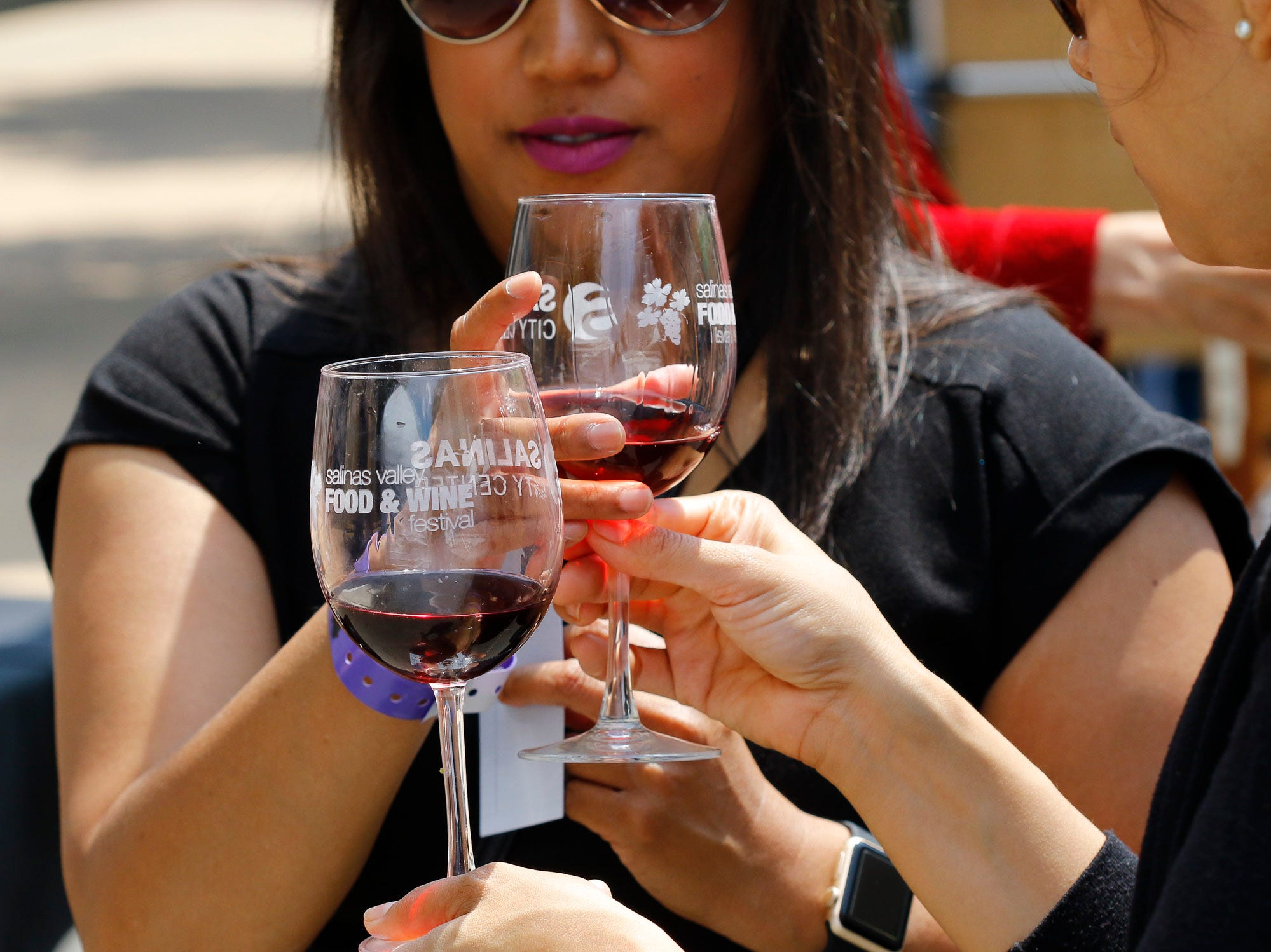 Attendees trade wine glasses during the 2018 Salinas Valley Food and Wine Festival which takes place on Main Street in Old Town Salinas on Saturday, August 11, 2018.