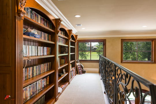 The upstairs balcony features scrolled ironwork on the railing and built-ins.