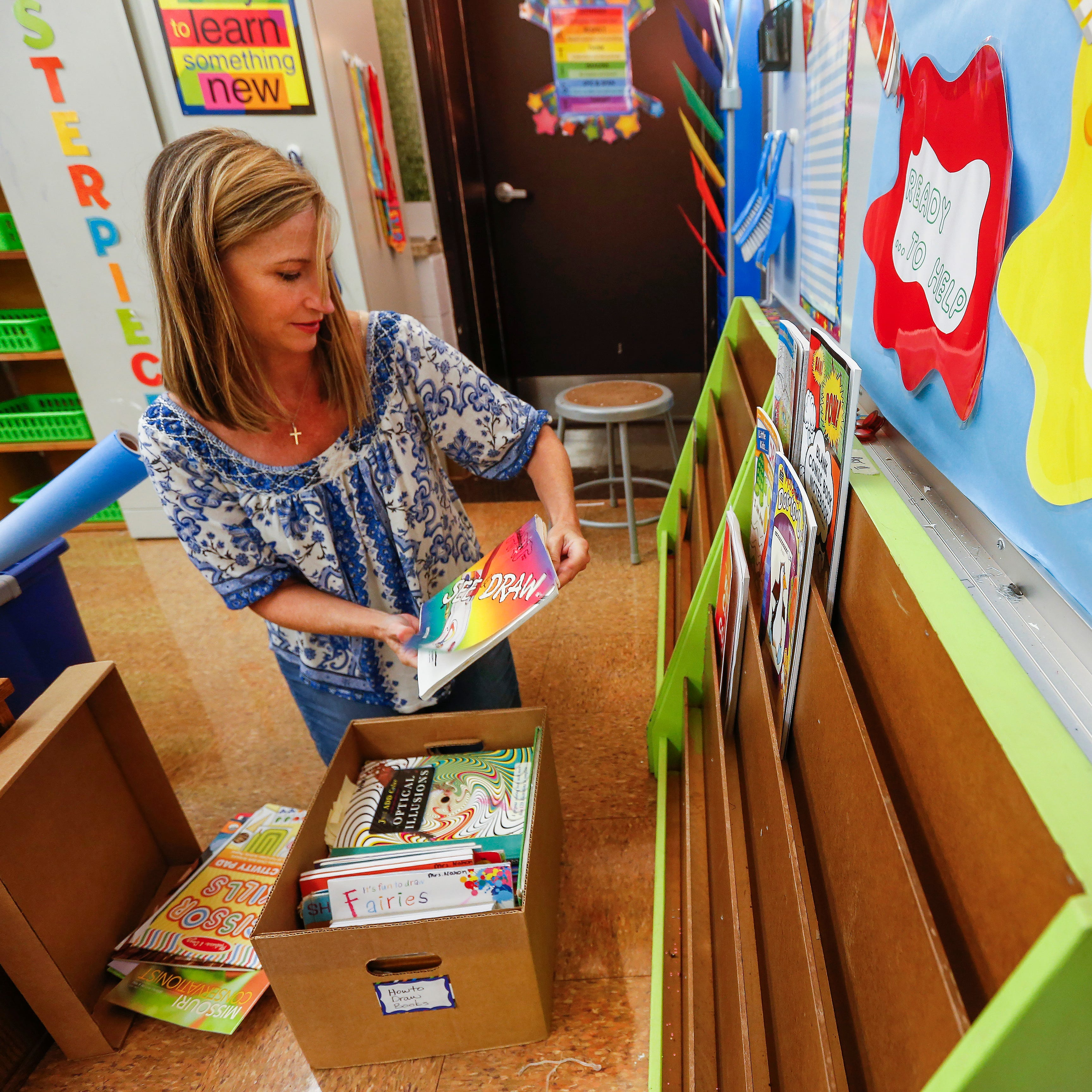 Angel Nahon, an art teacher at Jeffries Elementary School, gets her classroom ready for the first day of school.